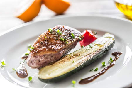 Roasted duck breast with zucchini tomato and parsley herbs.