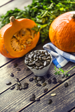 Roasted pumpkin seeds with raw pumpkins on wooden table.