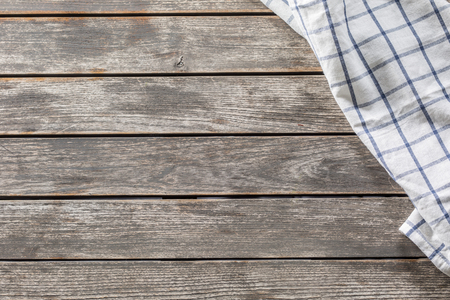 Blue white checketed tablecloth on wooden kitchen table - top of view. Stock Photo