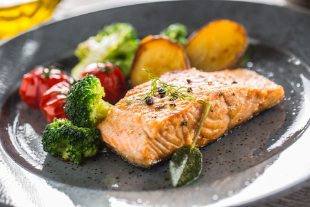 Roasted salmon fillet broccoli tomatoes and fried potatoes with dill cream sauce.