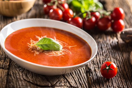 Hot tomato soup parmesan cheese and basil leave on old oal table. Stock Photo