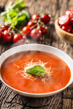 Hot tomato soup parmesan cheese and basil leave on old oal table. Banque d'images