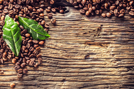 Top of view coffee beans and green leaves on rustic oak table. Foto de archivo - 122612633