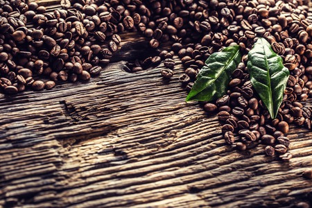 Top of view coffee beans and green leaves on rustic oak table. Foto de archivo - 122612634