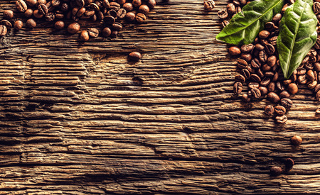 Top of view coffee beans and green leaves on rustic oak table. Foto de archivo - 122612643