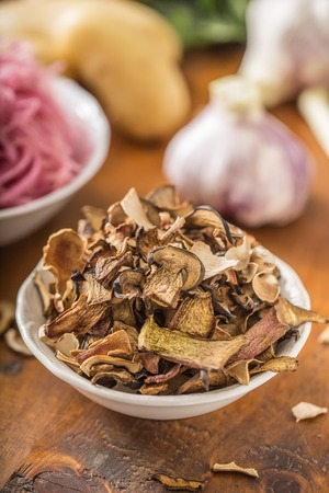 Dried mushrooms sour cabbage garlic and potatoes on wooden table.