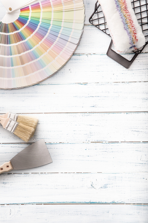 Color palette for painting with roller palette-knife and sifter on a wooden table - top of view.