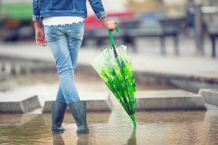 Young pre-teen girl stands with an umbrella in puddle after spring or summer rain.