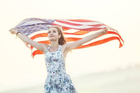 Young happy american woman holding USA flag. Reklamní fotografie