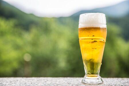 Helles Bier vom Fass auf Steintisch irgendwo in der Natur. Standard-Bild