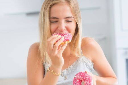 Young blonde girl eats pink donuts in home kitchen with taste emotions.
