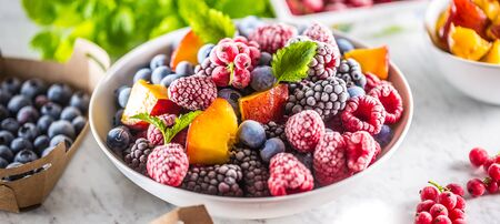 Frozen fruits blueberries blackberry raspberry red currant peach and herbs melissa. Фото со стока