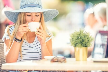 Beautiful girl drinking coffee in a cafe terrace. Summer portrait young woman. 版權商用圖片