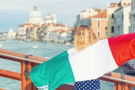 Tourist woman with italian flag on the bridge on Grand canal in Venice - Italy.