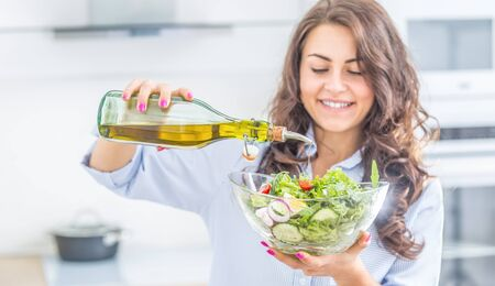 Young woman pouring olive oil in to the salad. Healthy lifestyle eating concept.