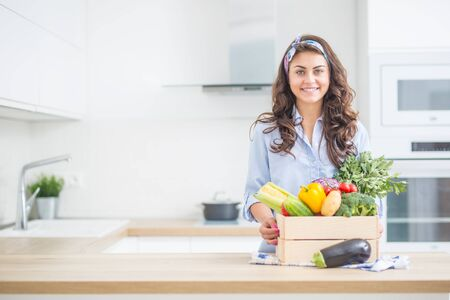 Woman in her kitchen with wooden box full of organic vegetable. Imagens