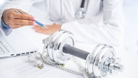 A doctor woman in surgeries prescribes sport movement and weight loss using dumbbells and a measuring tape.