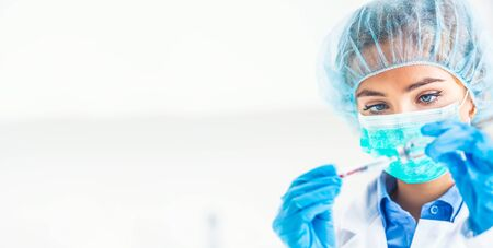 Female doctor working with syringe needle and ampoule of medicine. A scientist in sterile clothes is making a vaccine drug. Stock Photo