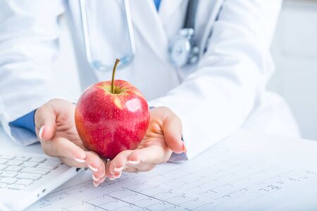 Woman doctor in ambulance holds red apple in hands. On desk laptop and EKG diagram.