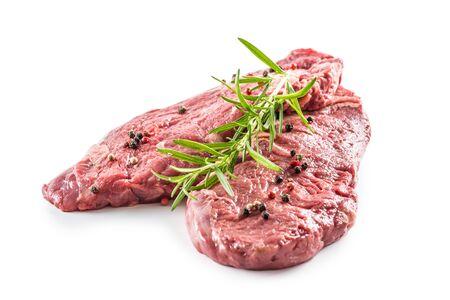 Mięso wołowe Rib-Eye stek z solą i pieprzem z rozmarynem na białym tle.