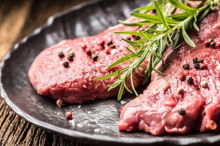 Beef meeat Rib-Eye steak wit rosemary salt and pepper on black plate. Stock Photo