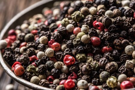 Mixed peppercorns red black and white in bowl - Close-up. Фото со стока