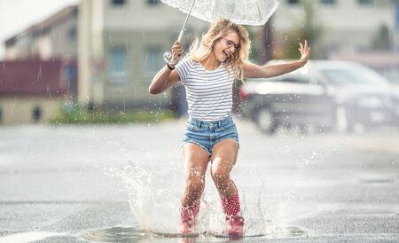 Fröhliches Mädchen, das mit weißem Regenschirm in gepunkteten roten Galoschen springt. Heißer Sommertag nach der Regenfrau, die in Pfütze springt und plant Standard-Bild