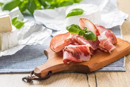 Pork ham prosciutto and camembert or brie cheese with basil leaves on table.