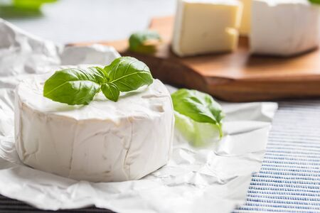 Camembert or brie cheese with basil leaves on table.