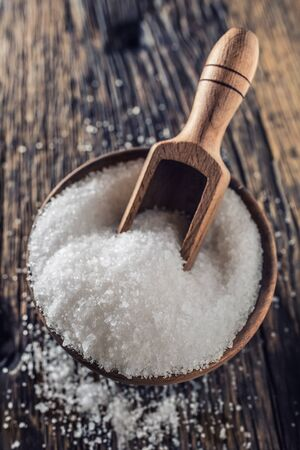 Coarse-grained salt in a wooden bowl with a ladle on an old oak table.
