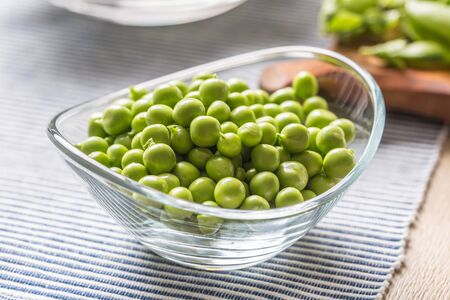 Fresh green pea seeds in bowl on kitchen table.