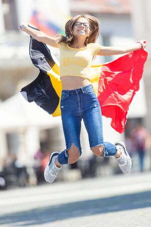 Attractive happy young girl with the Belgian flag. Imagens
