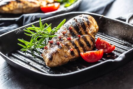 Chicken breast grilled with spices peper salt tomatoes and rosemary. 写真素材