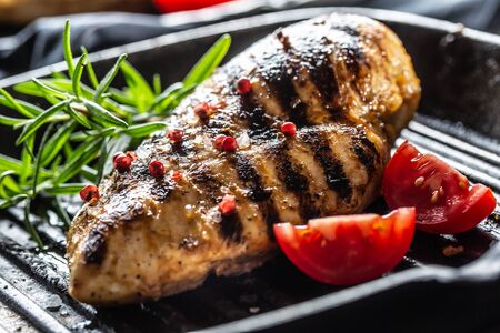 Chicken breast grilled with spices peper salt tomatoes and rosemary. 스톡 콘텐츠