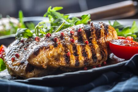 Chicken breast grilled with spices peper salt tomatoes and arugula.