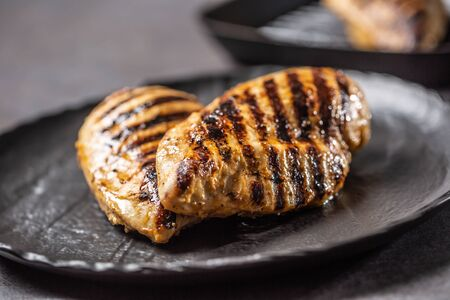 Grilled chicken breast in black plate on kitchen table.