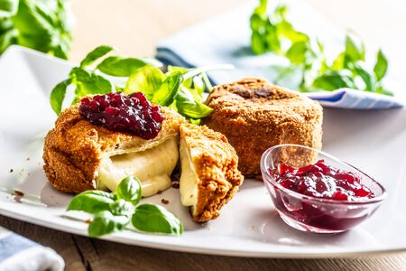 Fried camembert or brie cheese with cranberry jam and basil.