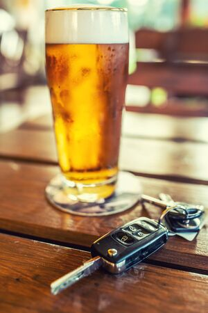Car keys and glass of beer or distillate alcohol on table in pub or restaurant. Banco de Imagens - 129340993
