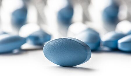 Blue pills loose lying on a white isolated background.