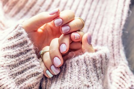 Art nail manicure for bride in purple sweater. Gel nails in soft pink color. 写真素材