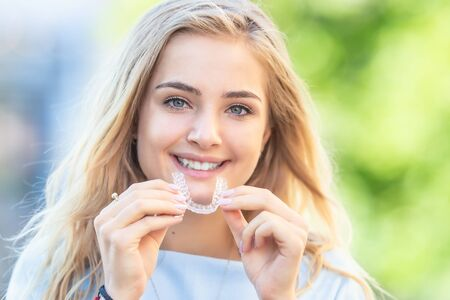 Invisalign orthodontics concept - Young attractive woman holding - using invisible braces or trainer.