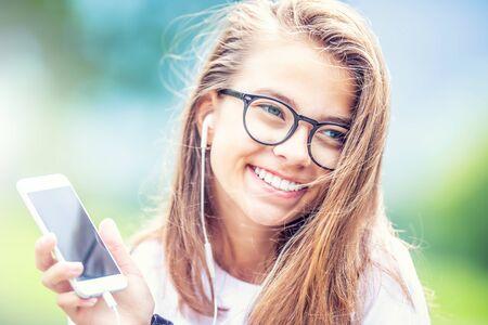 Joven adolescente con auriculares disfrutando con buena música. Mujer joven moderna con teléfono móvil. Foto de archivo