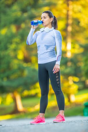 Young female athlete drinks water after training.