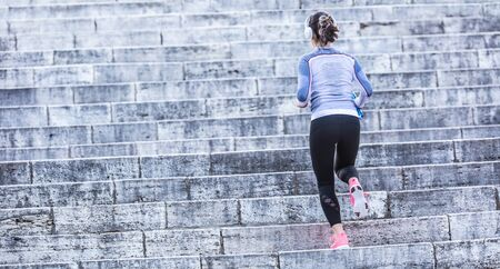 Young woman doing sports and running up the stairs.