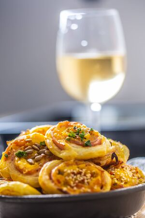 Rolls of puff pastry with ham bacon cheese sesame in dish.