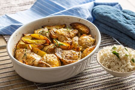 Chicken legs roasted with american potatoes in baking dish.