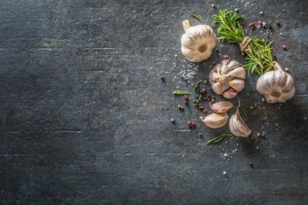Garlic cloves and bulb with fresh rosemary salt and spice on concrete table - Top of view.