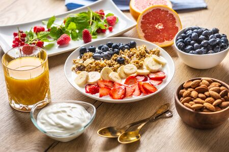 Healthy breakfast served with plate of yogurt muesli blueberries strawberries and banana. Morning table granola almonds berries citrus fruits juice and green herbs.