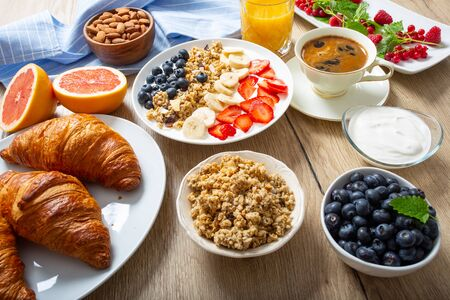 Healthy breakfast served with plate of yogurt muesli blueberries strawberries and banana. Morning table granola almonds berries citrus fruits juice coffee croissants and green herbs.