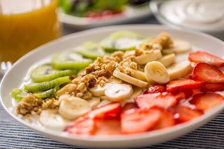 Healthy breakfast served with plate of yogurt muesli kiwi strawberries and banana. Morning table granola almonds berries juice and green herbs. 스톡 콘텐츠
